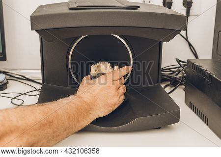 Close-up View Of A Mans Hand Introducing A Dental Mould Into A Scanner In A Laboratory