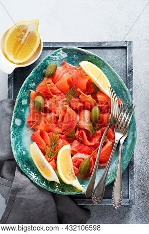 Slices Of Lightly Salted Salmon With Capers, Lemon And Dill On A Ceramic Plate On A Gray Concrete Ba