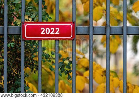Metal Sign With Digits 2022 On A Decorative Metal Fence, Background With Defocused Autumn Trees
