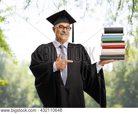 Mature man in a graduation gown holding a pile of books and pointing, posing in a park outdoors