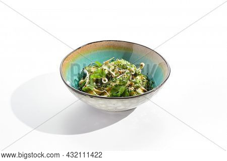 Chinese smashed cucumber with greens and sesame oil. Healthy vegetarian green salad with cracked cucumber and fresh green leaf. Healthy salad recipes concept. Salad bowl isolated on white background