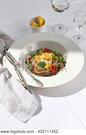 Beef tongue salad dressing with horseradish sauce and fresh green leaves. White restaurant plate with silverware on white table with glass. Meat salad bowl with vegetable. Salad restaurant dish