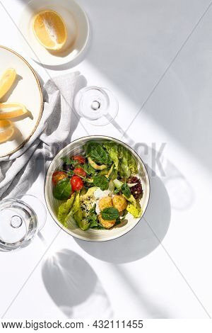 Salad bowl with avocado, tomato and cheese balls. Healthy vegetarian lunch with water glass on white table. Summer day dinner, sunlight and harsh shadow. Healthy salad bowl food. Organic salad bowl