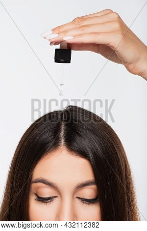 Cropped View Of Young Woman With Shiny Hair Applying Treatment Oil On Top Of Head Isolated On Grey