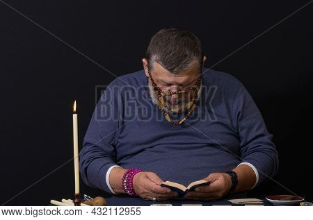 Nice Low Key Portrait Of Senior Man - Soothsayer  Reading Small Book Before Doing Cartomancy