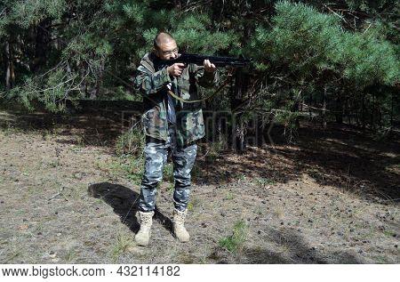 Mature man with Turkish 12-gauge rifle Hatsan Escort MP(pump action shotgun). Unformal shooting range near Kiev. September 6,2021. Kiev Region, Ukraine