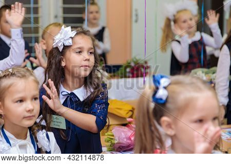 First Graders In The Classroom Perform A Warm-up While Standing. She Is In Grade 1 School.