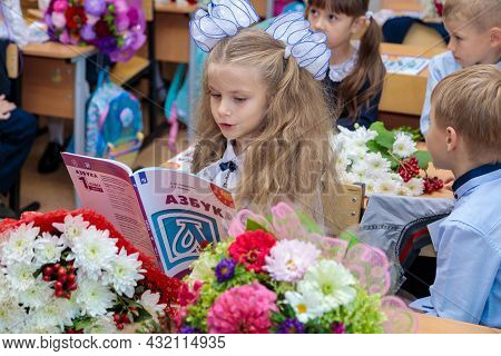 The First Grader Sits At Her Desk In The Classroom And Reads The Alphabet. A Girl With White Bows Si