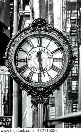 B&w Photo Of The Fifth Avenue Building Street Clock Near Buildings With Fire Escapes On A Blurry Bac