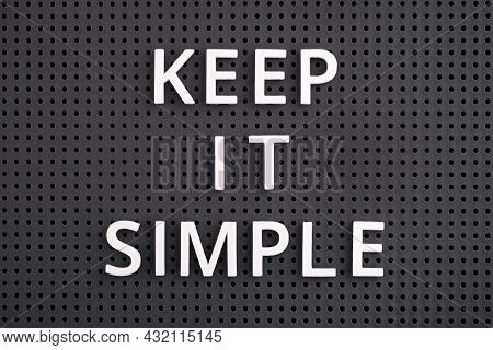 A Phrase Keep It Simple Spelled Out With White Letters On A Gray Pegboard. Close-up.