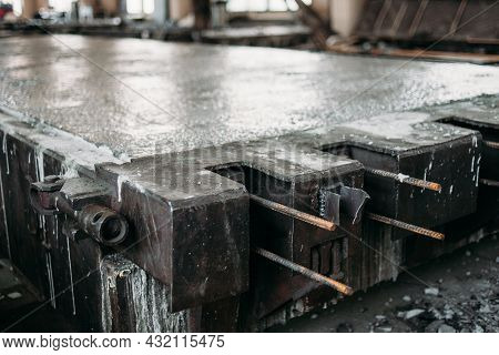 A Loaded Concrete-filled Metal Mold For The Production Of A Reinforced Concrete Road Slab Is Located