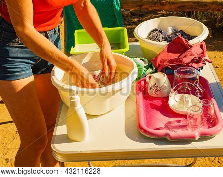 Mature Woman Washing Up Dishes In Bowl On Fresh Air At Camper Car. Dishwashing Outdoor On Camping Si