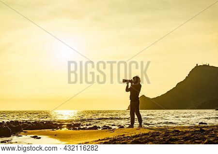 Tourist Woman With Camera Take Travel Picture On Monsul Beach At Sunset. Cabo De Gata Nijar Natural