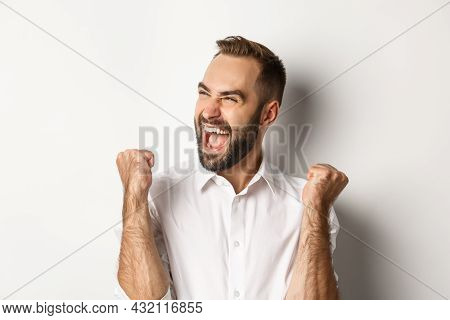 Close-up Of Successful Caucasian Man Rejoicing, Making Fist Pump And Shouting Of Joy, Looking Left,