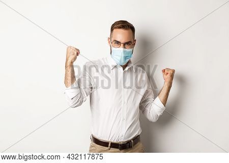Covid-19, Social Distancing And Quarantine Concept. Confident Business Man In Medical Mask Fist Pump
