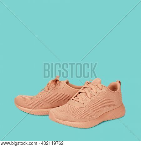 Modern sneakers gym shoes isolated on pastel green background. Sport activity recreation footwear concept. Casual style for sports and leisure