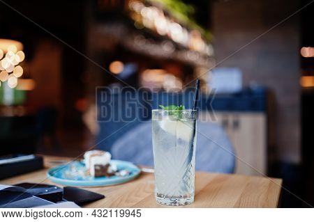 Cool Freshly Made Lemonade In Glass On Wooden Table At Restaurant.