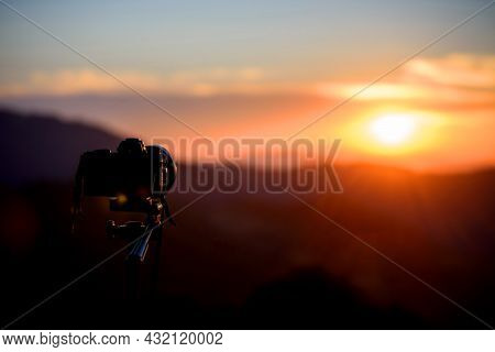 Camera On Tripod And Photography View With Blurred Focus Mountain Landscape. Sunset Or Sunrise Light