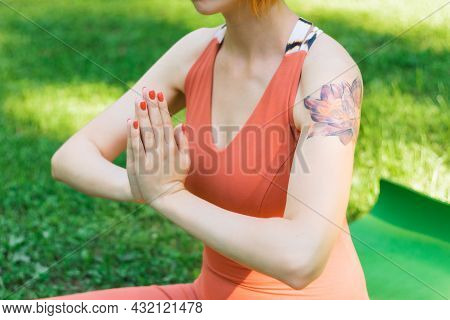 Kyiv, Ukraine 08.08.2021: Girl Sitting In Lotus Position With Her Arms Folded On Her Chest In Namast