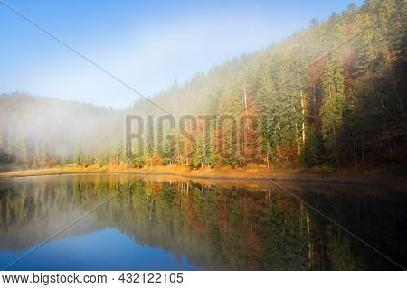 Morning Landscape At The Mountain Lake. Beautiful Autumnal Nature Scenery With Fog. Coniferous Fores