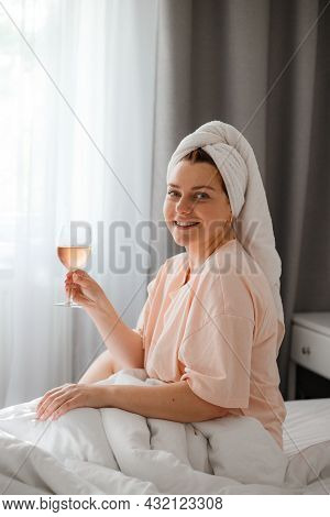 Beautiful Happy Young Woman After Shower With Glass Of Wine In Bedroom. Staying At Home In Isolation