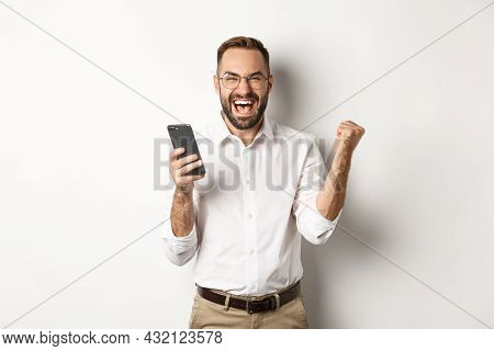 Successful Businessman Looking Happy, Fist Pump And Rejoice In Winning Online Lottery, Standing Over
