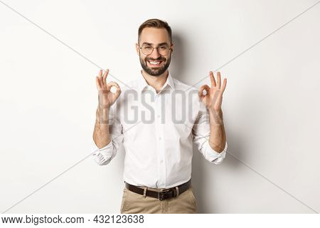 Satisfied Handsome Businessman Showing Ok Sign, Gurantee Quallity, Standing Pleased Against White Ba