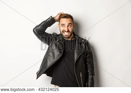 Confused Macho Guy In Black Leather Jacket Looking Awkward And Unsure, Scratching Head Puzzled And S