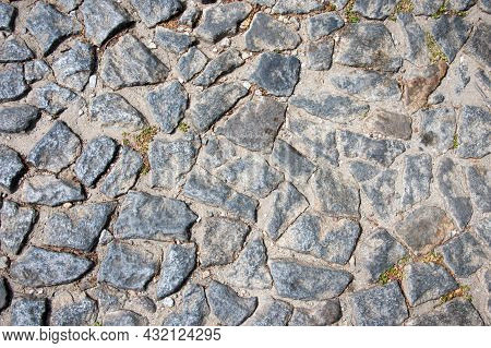 Stone Pavement Texture With Little Plants Growing Among Them. Portugal