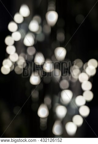 Round And Triangular Bokeh On A Black Background. Abstract Background With Bokeh Defocused Lights. V