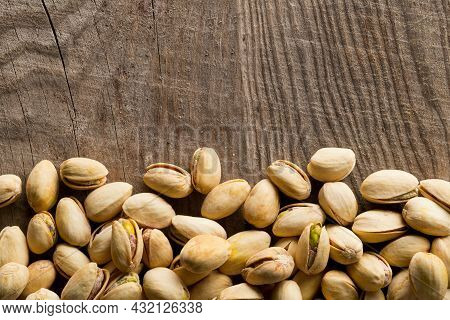 Border Of Salted, Roasted Green Pistachio Nuts Snack On Wood Background, Healthy Food Snack, Copy Sp