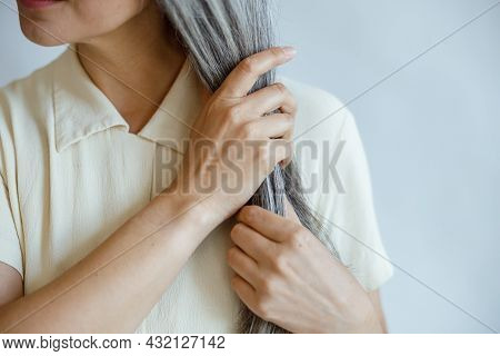 Middle Aged Lady In Elegant Blouse Holding Straight Grey Hair Poses On Light Grey Background