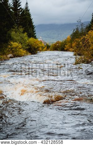 The Flow Of Turbulent Water In Autumn. A Mountain Stream Flows Among The Rocks Of Stones. Autumn Riv