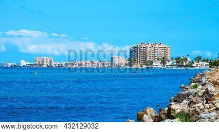La Manga, Spain - July 29, 2021: A view of the Matas Gordas beach in the northwest section of La Manga del Mar Menor, in Murcia, Spain, highlighting some apartment blocks next to the Mar Menor lagoon