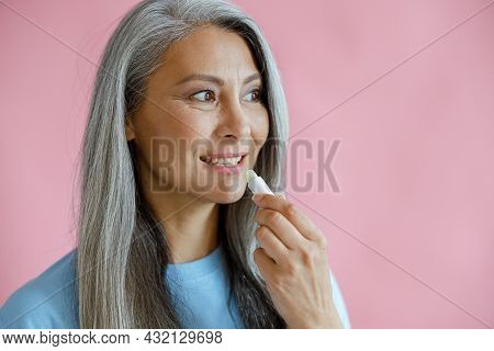 Positive Silver Haired Asian Woman Applies Lip Balm On Pink Background
