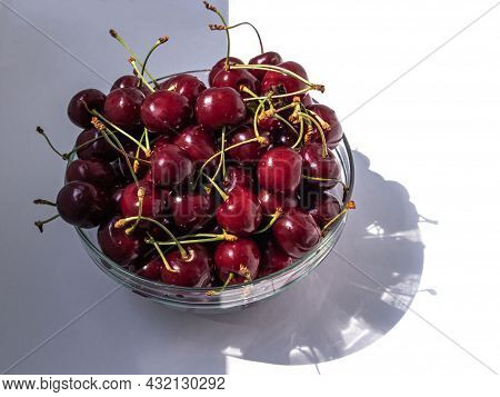 Sweet Cherries In A Transparent Bowl In Partial Shade