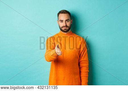 Confident Man Extending Hand For Handshake, Greeting You, Looking Self-assured, Standing Over Light