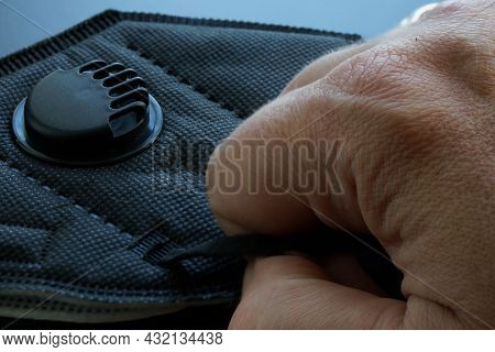 A Man's Hand Holds A Black Medical Respirator With Filter And Valve. Respirator Protection Class Kn9