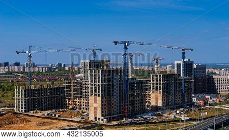Construction Cranes And Houses Under Construction. Construction Of A New High-rise Buildings In Resi