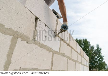 Worker Wipes The Seams With A Spatula Outside The House Of Blocks, Bottom View. Bricklayer Worker La