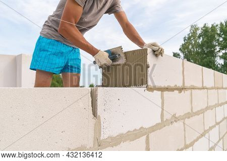 Builder Uses A Notched Trowel To Apply The Cement Mixture To The Aerated Concrete Blocks. Concept Of