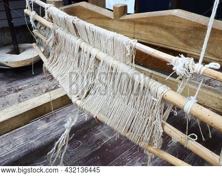 Loom And Threads. Antique Equipment For The Production Of Carpets, Clothing And Woven Household Item