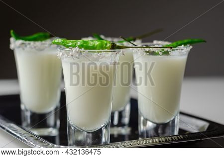 Coconut Cocktail In Drink Shot Glass Decorated With Coconut Flakes And Green Bird Eye Chilli Served