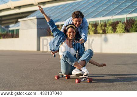 Man And Woman Have Fun On Longboard: Cheerful Male Push Joyful Female Sitting On Skateboard And Laug