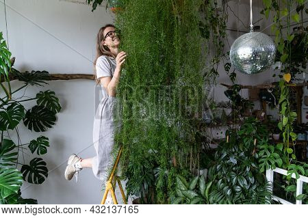 Happy Young Woman Florist In Lien Dress, Embracing Lush Asparagus Fern Houseplant In Flower Store. S