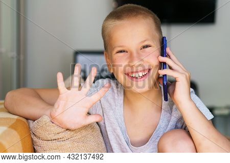 Happy Little Boy Having Fun Playing Game On Mobile Phone, Preschool Child Sitting On Sofa With Smili