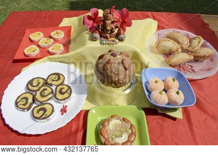 Selective Focus Of Lord Ganesha With Variety Of Assorted Indian Sweets Made For Prashad And Offered