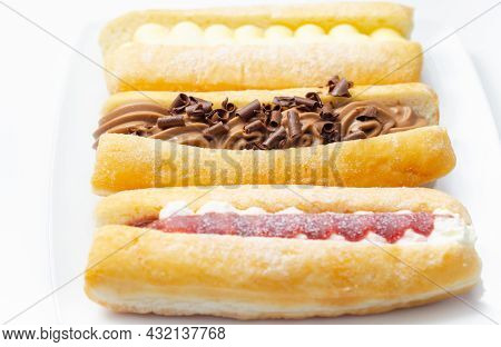 Mixed Finger Donuts Filling Chocolate, Custard, Jam And Whipped Cream, Eclairs In Different Flavors,
