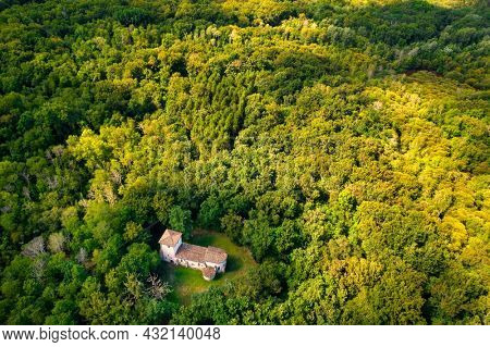Aerial view of the old pilgrimage church of Lugo buitl in the middle of the forest. Gironde, France