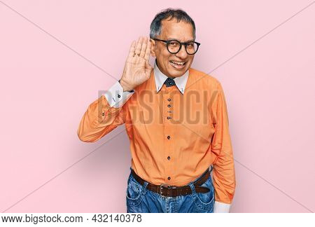 Middle age indian man wearing casual clothes and glasses smiling with hand over ear listening an hearing to rumor or gossip. deafness concept.